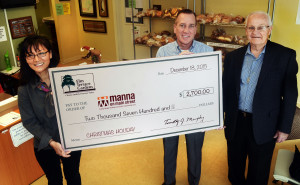 Geoff Patton--The Reporter Manna on Main Street Development Officer Paige Harker, left, accepts a donation to Manna from Elm Terrace Gardens on behalf of the Resident's Council Friday, December 18, 2015.  At center is Tim Murphy, Elm Terrace Gardens CEO, and at right in Frank Ferris, Resident's Council President.